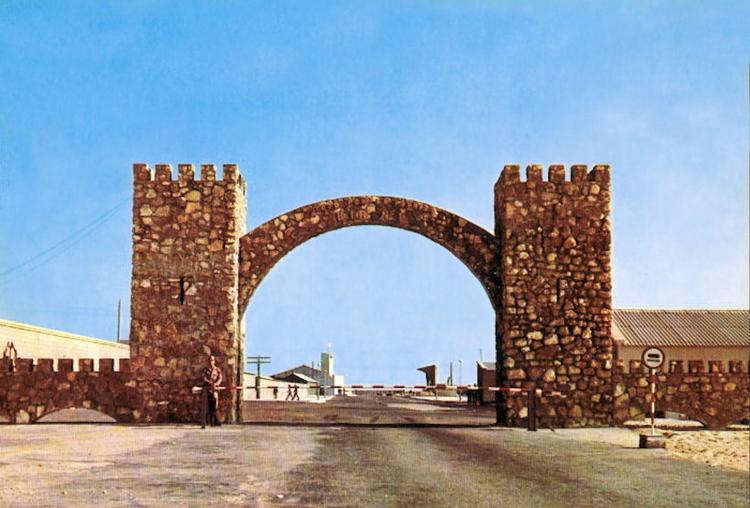 03-01.- El arco de entrada a El BIR, el arco más famoso del Sáhara. Dicen que se edificó para poder colgar en él lo que había que colgar a la entrada. Entre este arco, el océano y el Campo de Margaritas, se sufría una dura instrucción. Postal: 1975