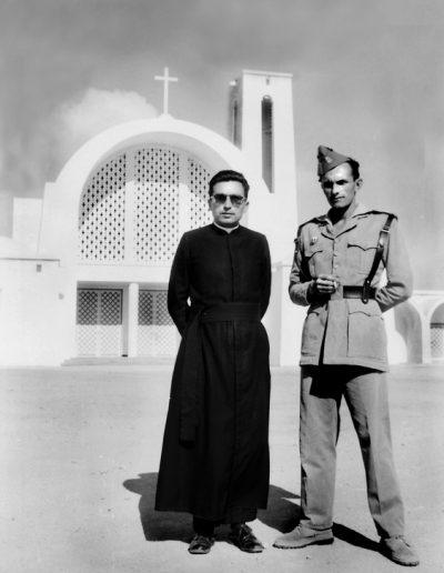 04-10a.- Sacerdote y oficial frente a la iglesia de El Aaiún. Foto: Joan Bordas. El Aaiún, 1958