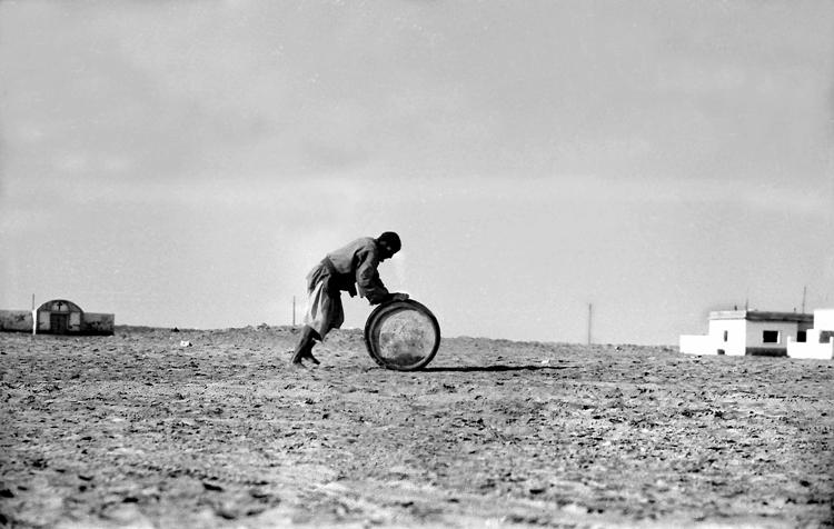 06-03c.- Saharaui rodando el bidón hacia la jaima. ¿Con agua? Foto: Joan Bordas. Villa Bens, 1957