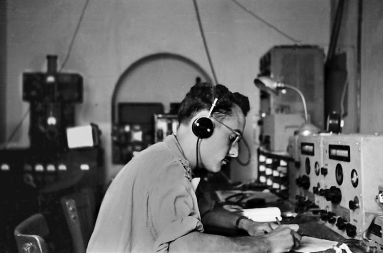 09-06.- Recibiendo malas noticias, Estación receptora de radio de base Marconi CR-150 de la Red Permanente. Al fondo a la derecha la estación emisora. Los equipos estaban duplicados. Foto: Joan Bordas. Villa Bens, 1957